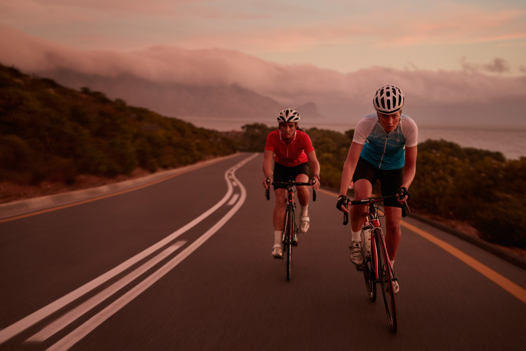 Pro female cyclists sprinting on road bikes at  last light
