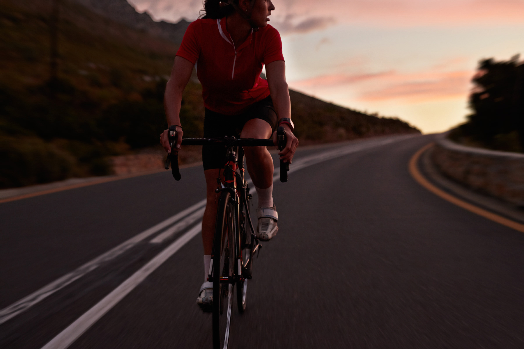 Female pro cyclist looking back while riding at sunset