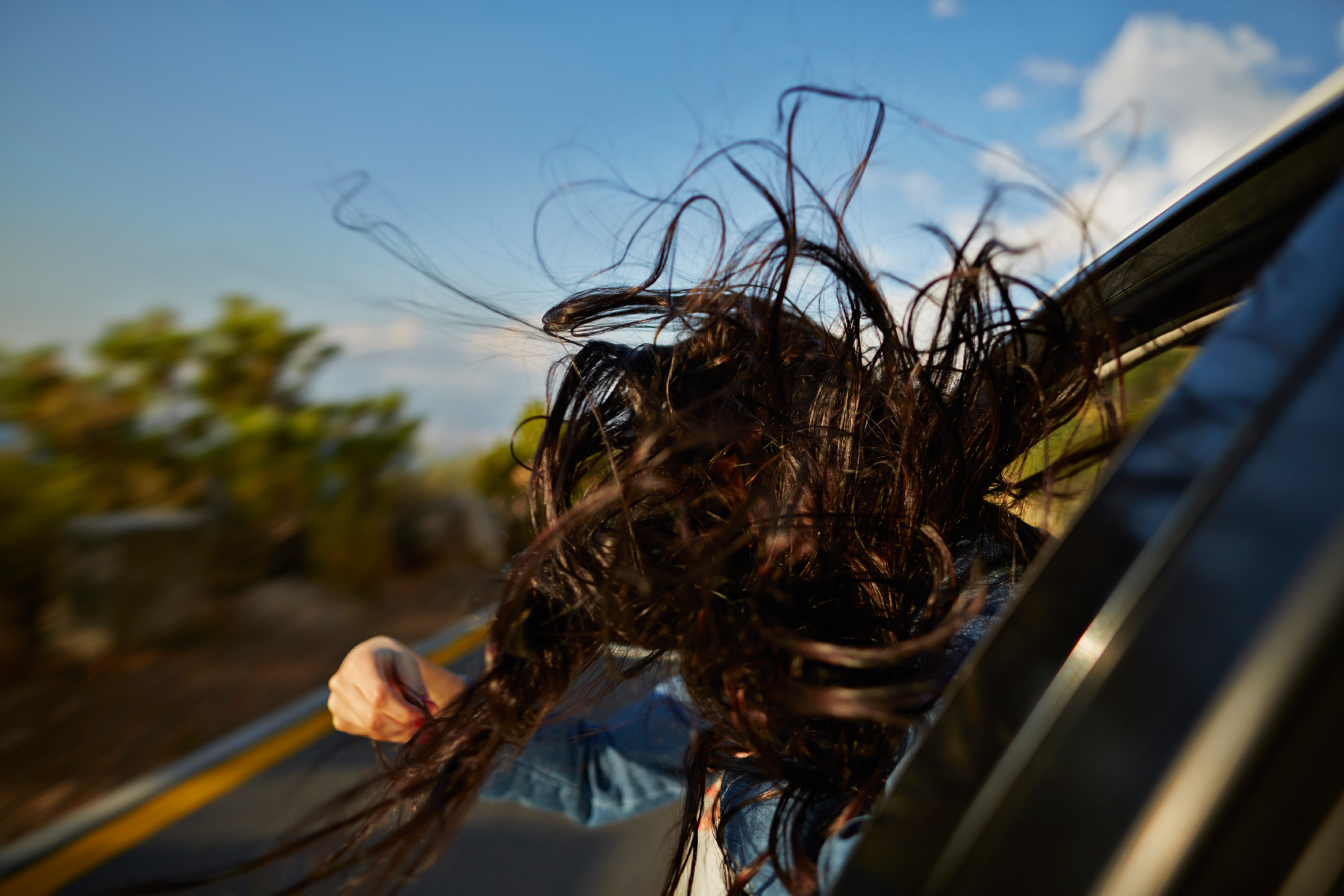Long hair sticking out of car blowing in the wind