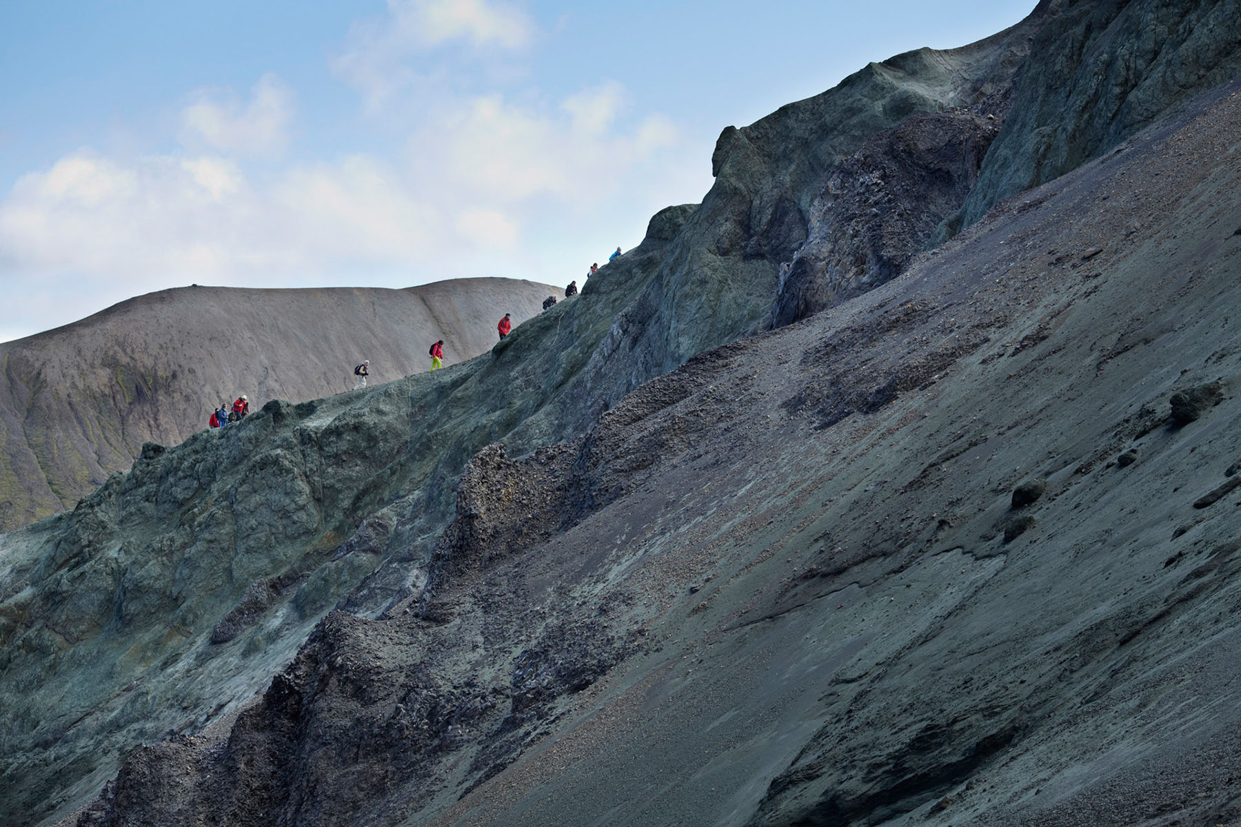 Hikers walking up on ledge of mountain