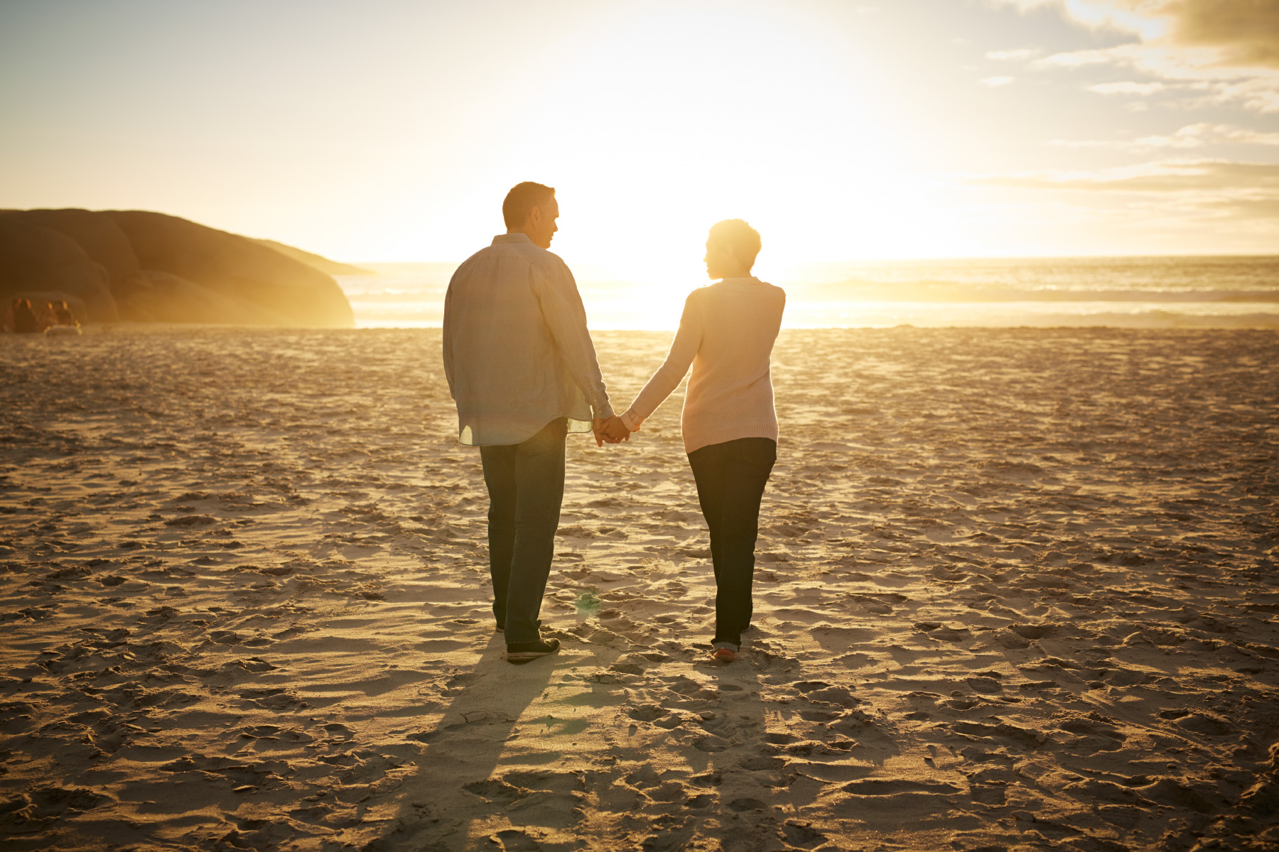Senior couple hand in hand at beach sunset