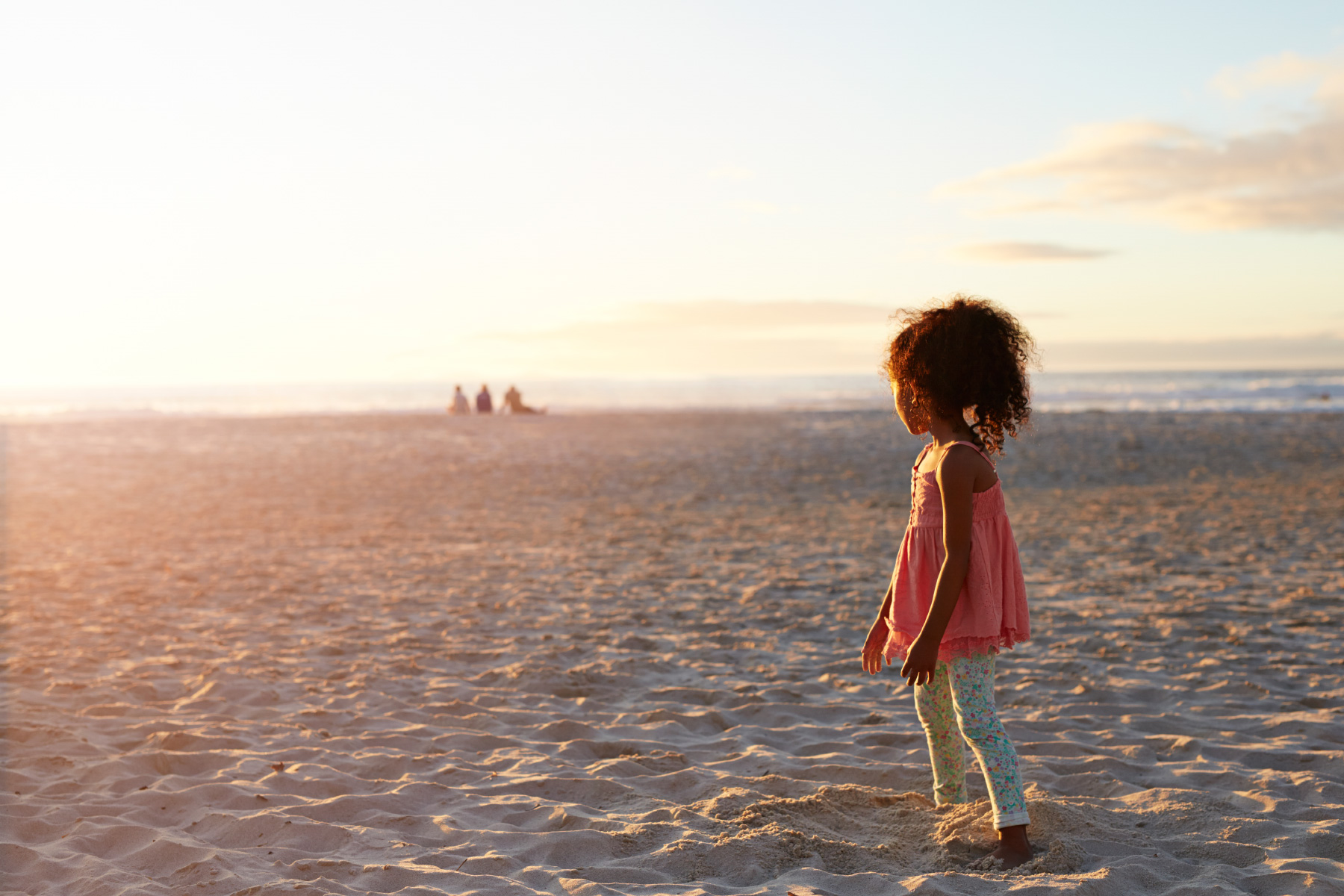 Little girl looking at sunset by the beach