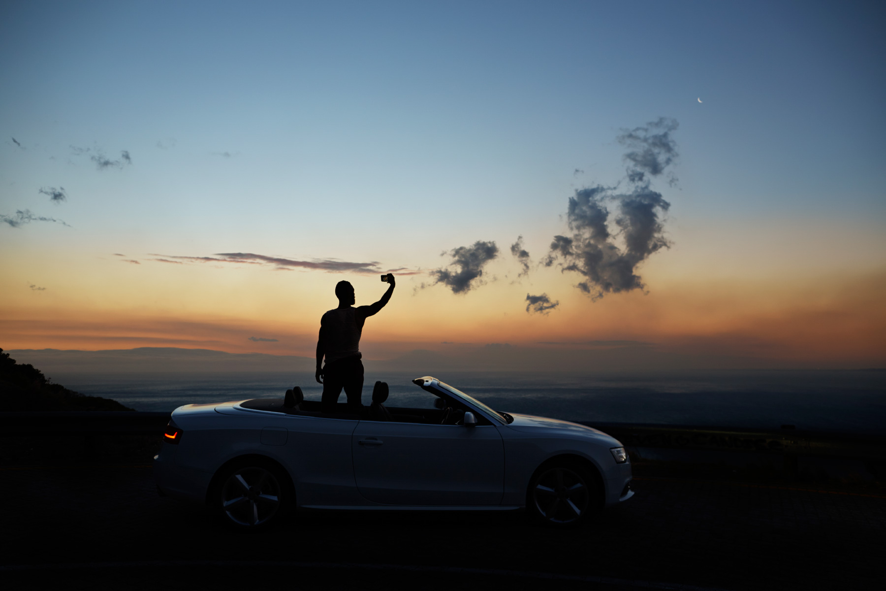 Man taking picture of sunset in his convertible car