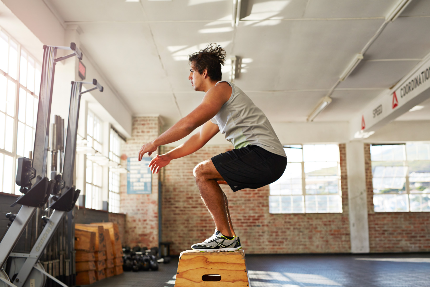 Man doing box jump in crossfit center