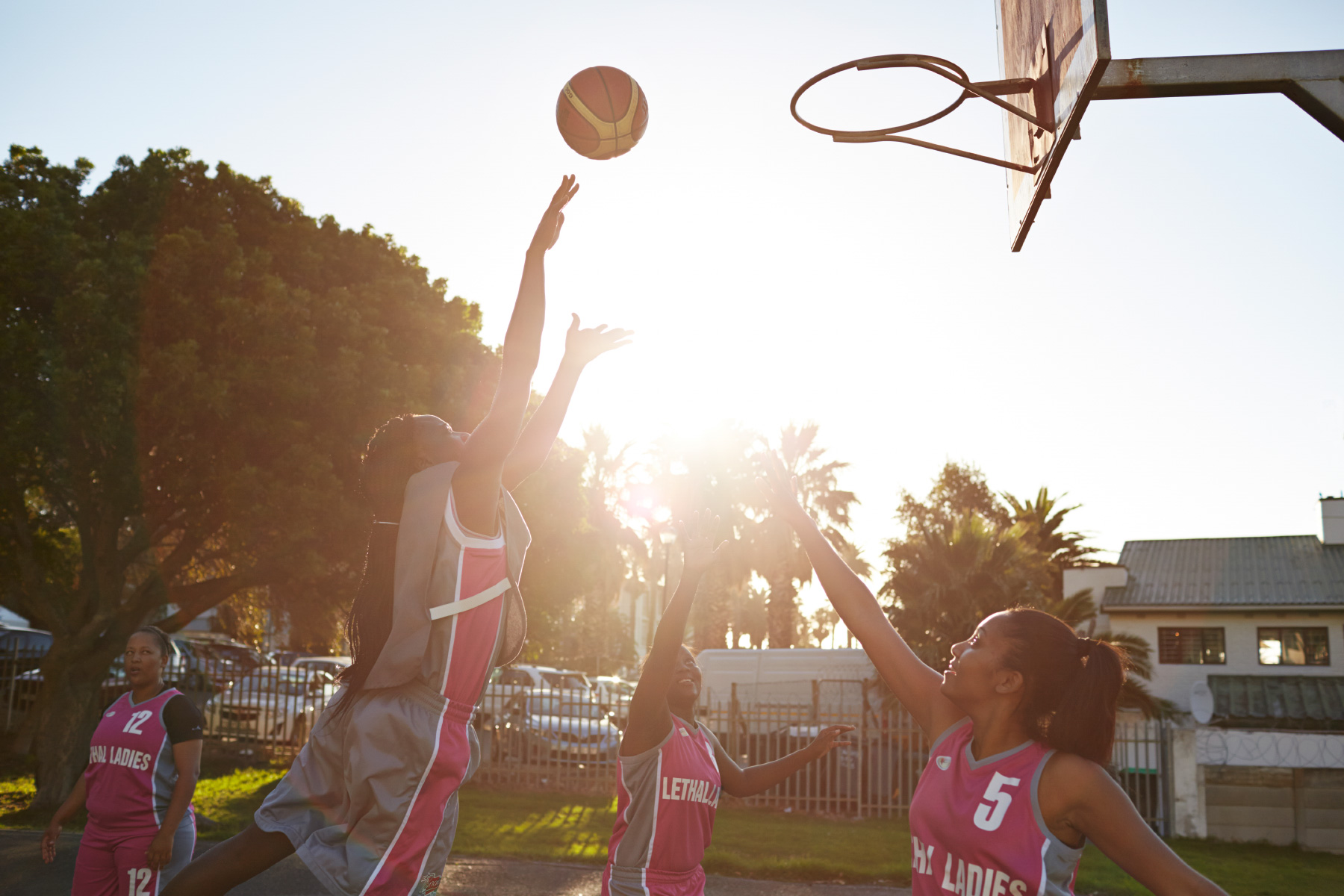 Female amateur basket team scoring goal at sunset