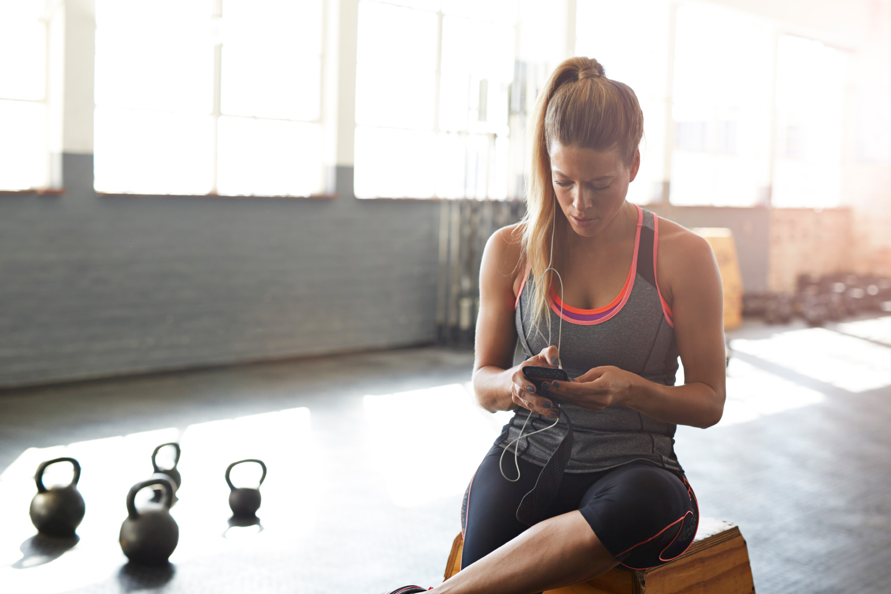 Woman checking smartphone in gym
