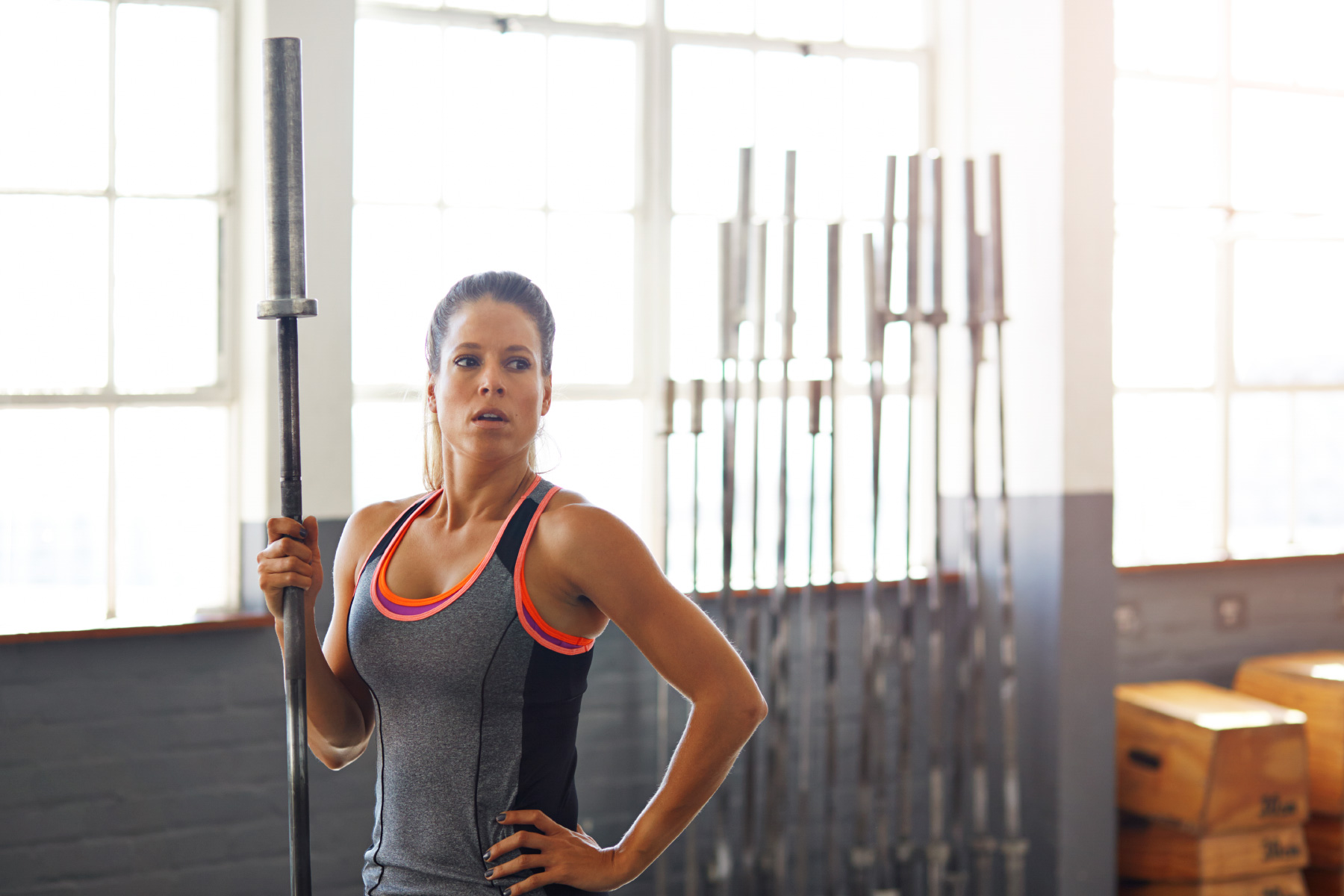 Exhausted woman holding on to barbell in crossfit gym
