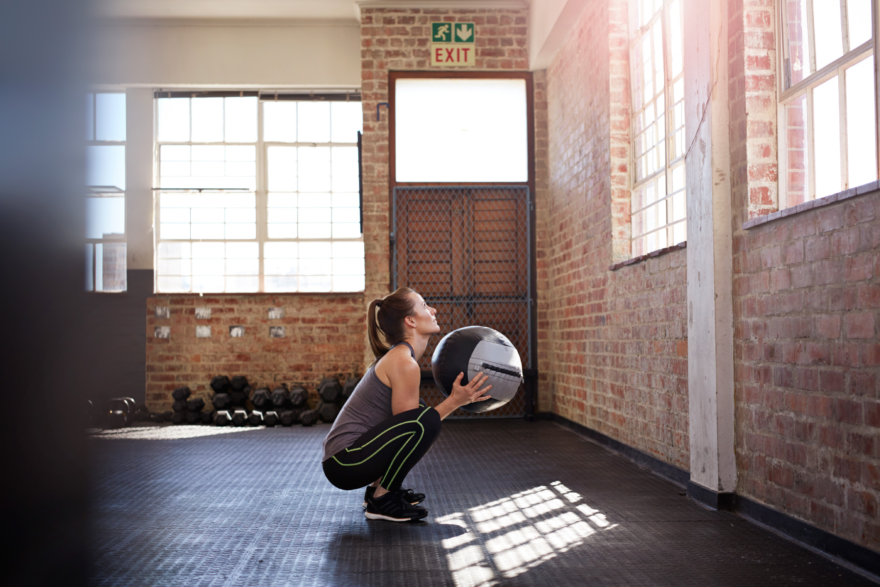 Woman doing squad with ball in crossfit gym