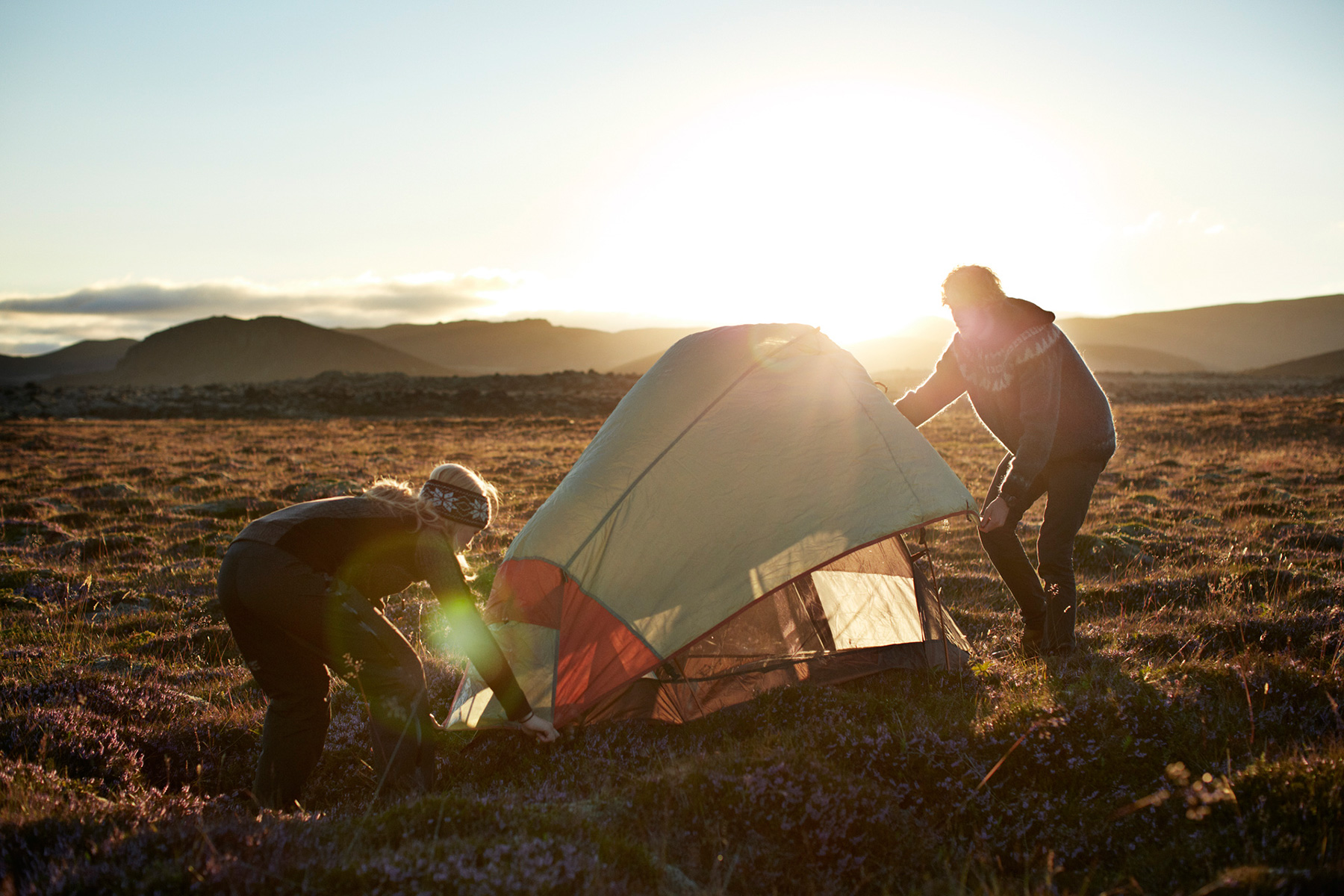 Outdoor couple setting up tent in the sunset in Iceland
