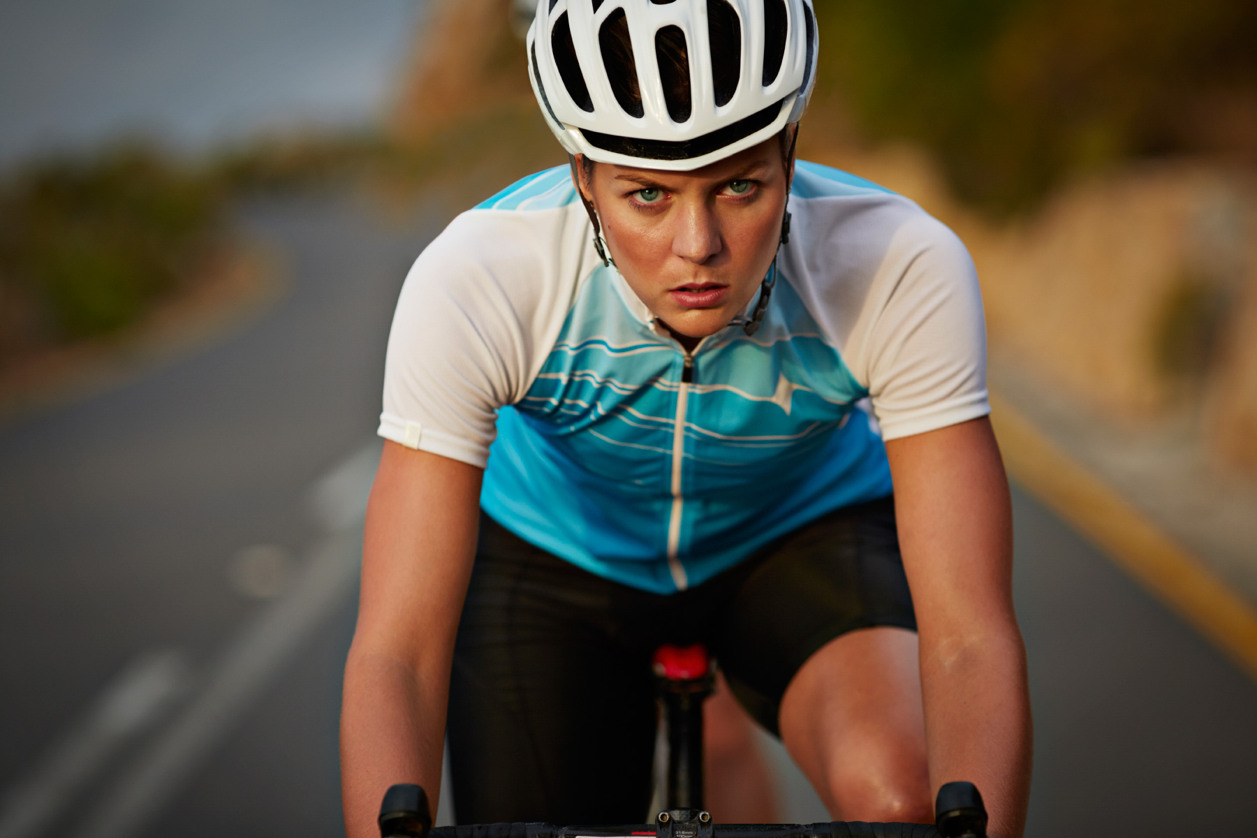 Portrait of pro female bike rider riding down mountain
