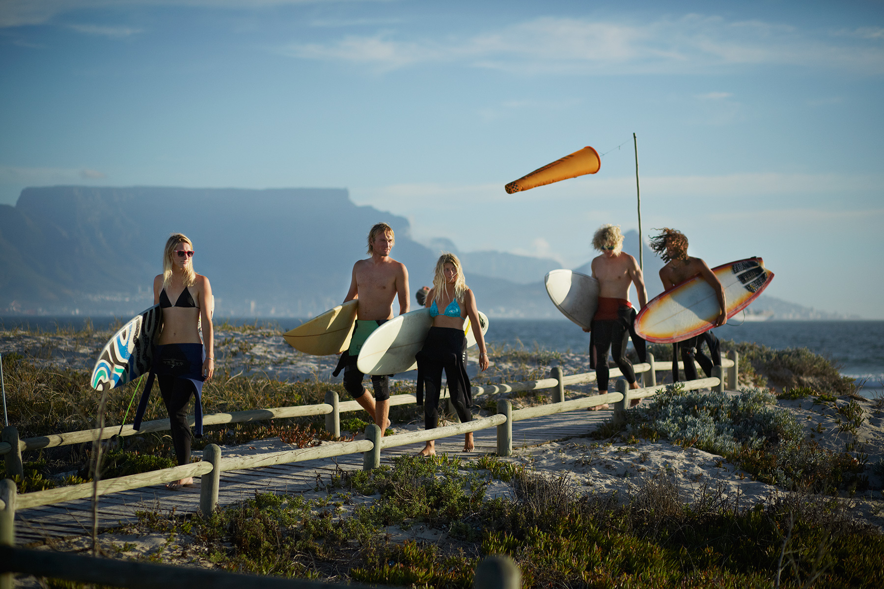 Group of surfers walking with surfboards