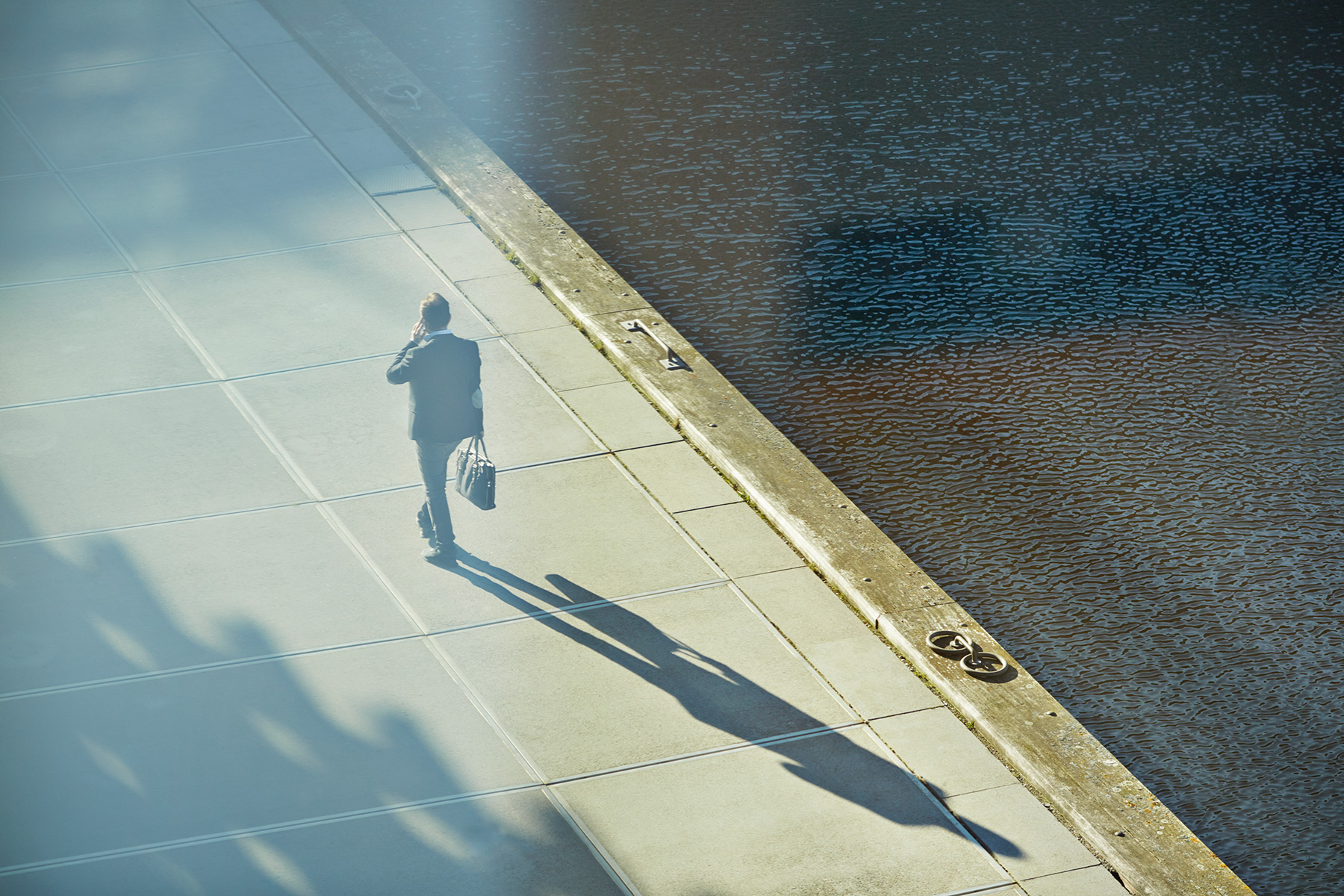 Businessman walking with phone, casting long shadow