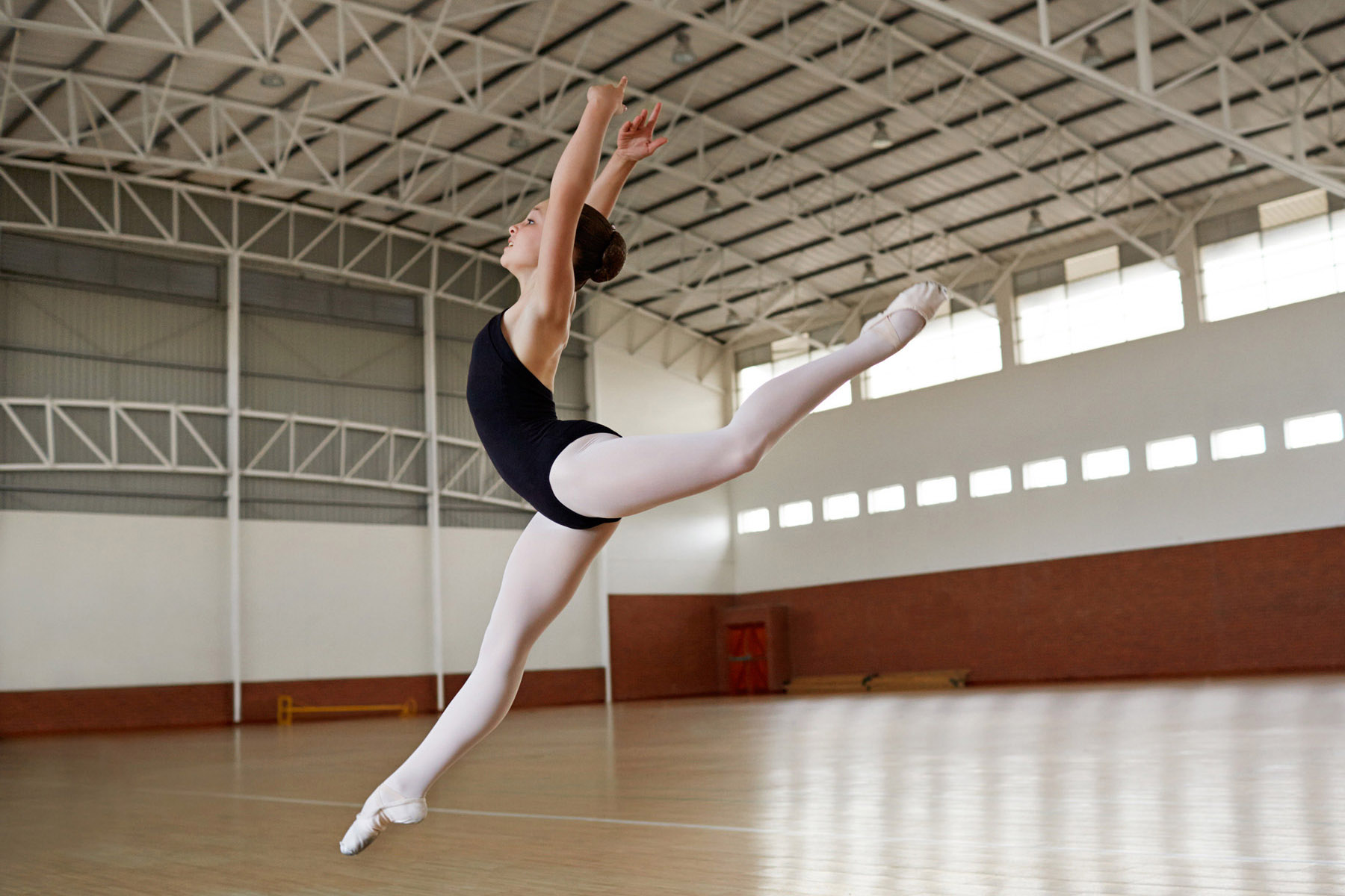 Ballet dancer making elegant jump at practice