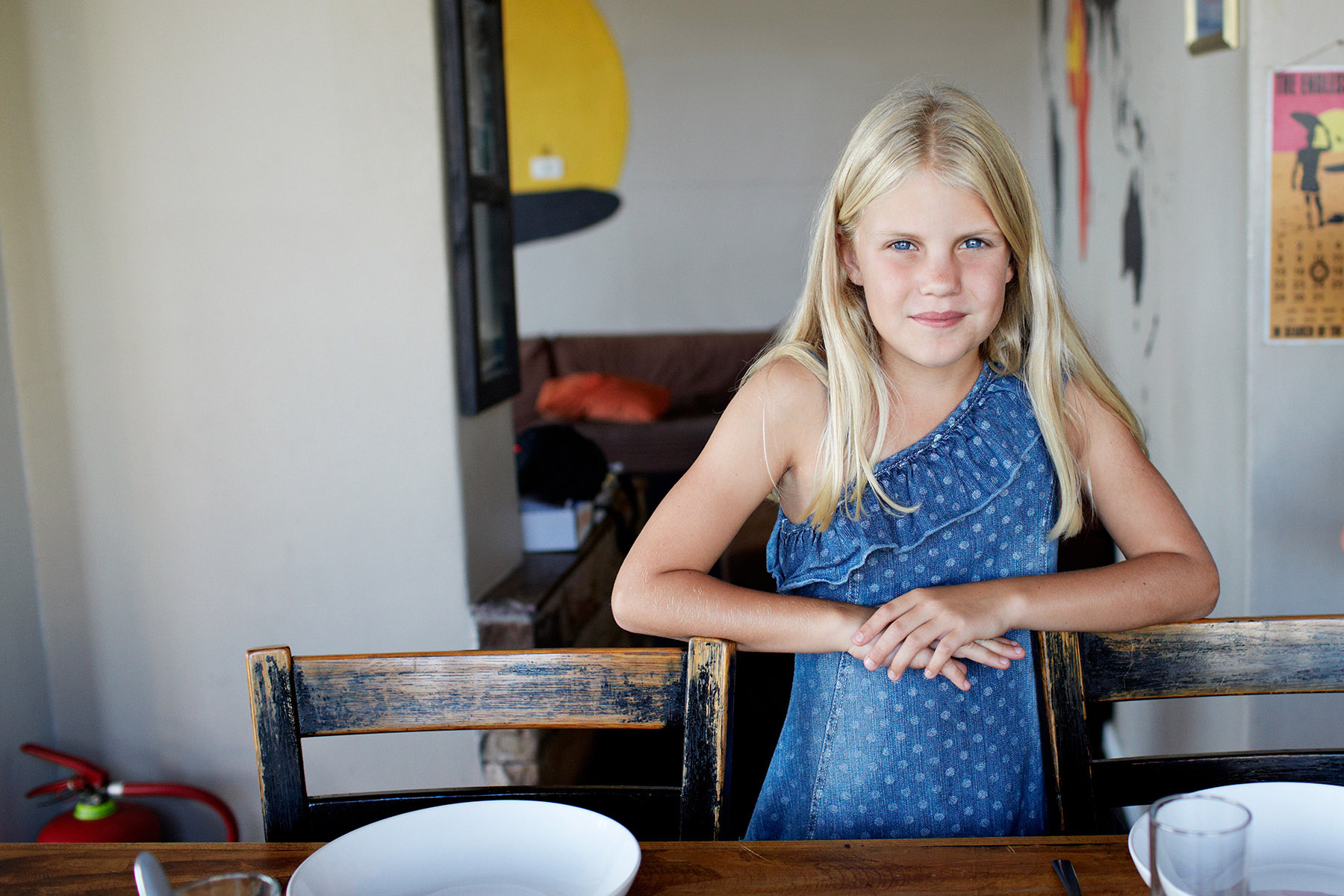 Portrait of girl standing by dinner table in surfer house