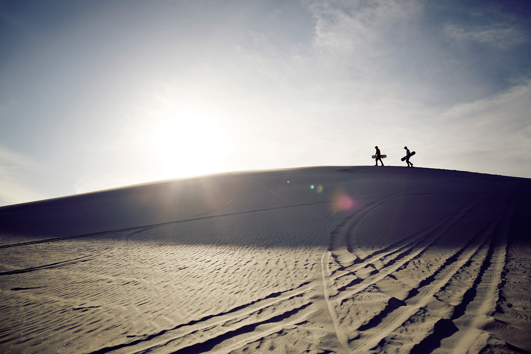 Two sand boarders walking on the edge of sand dune at sunset