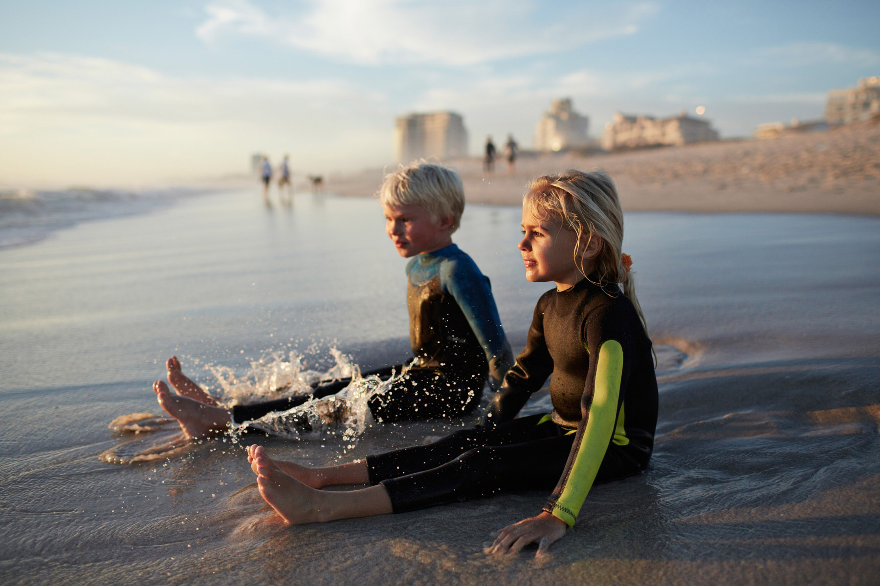 Surf kids in wetsuits relaxing in the shallows