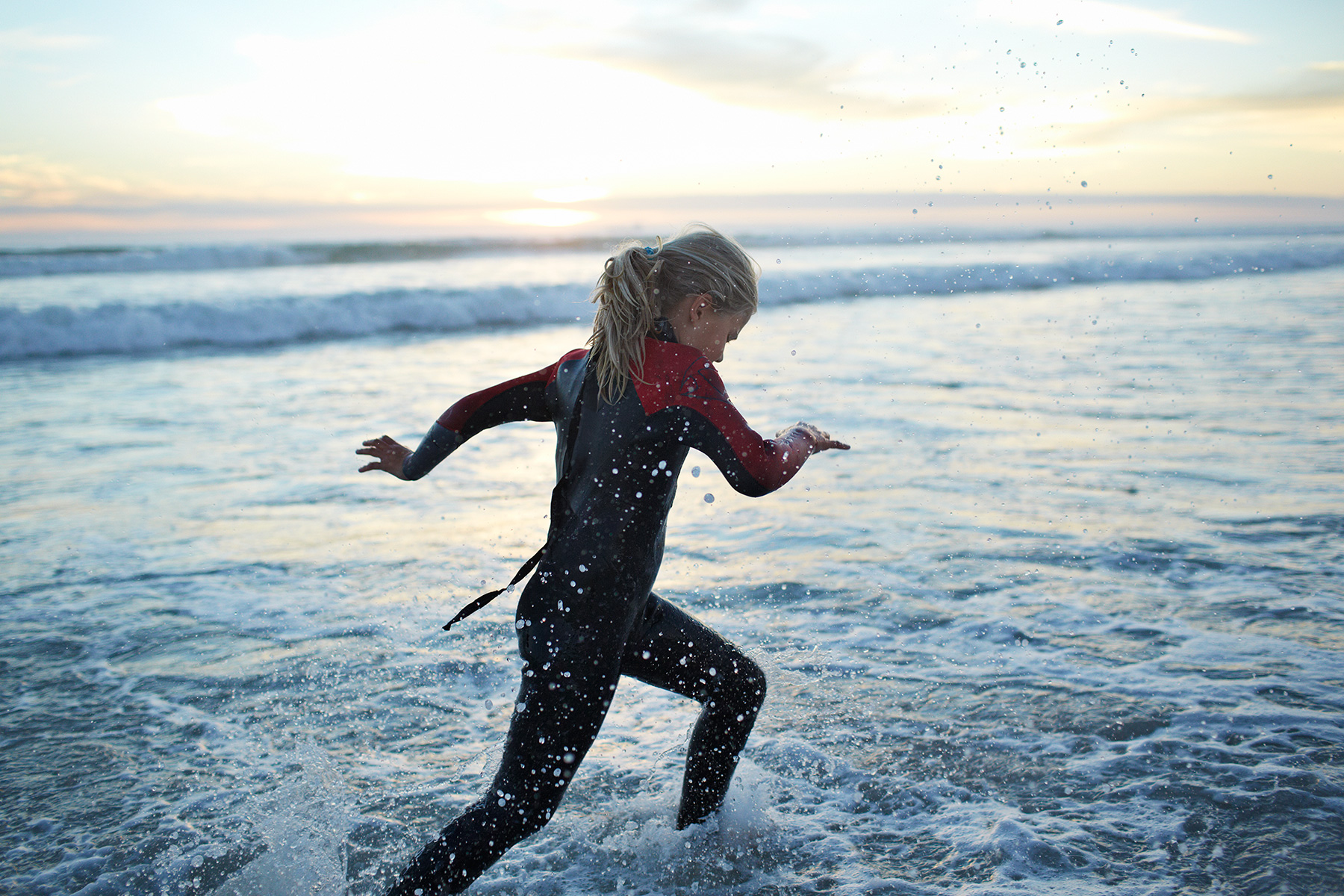 Surfer girl running in ocean