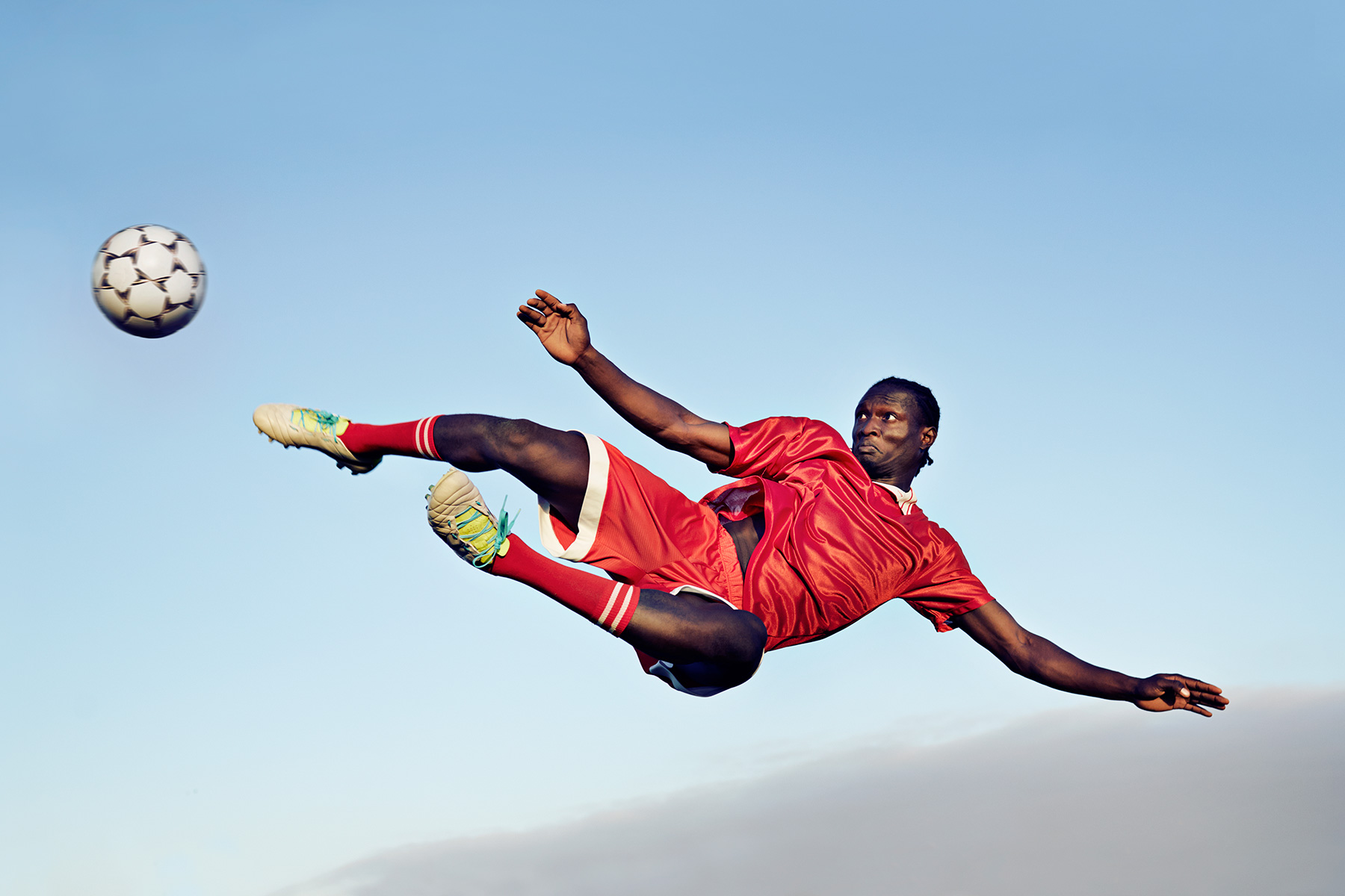 Soccer player jumping & kicking ball in the air (football)