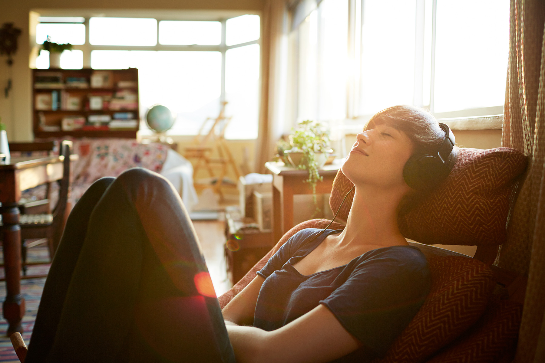 Woman with headphones relaxing at home in the sunset