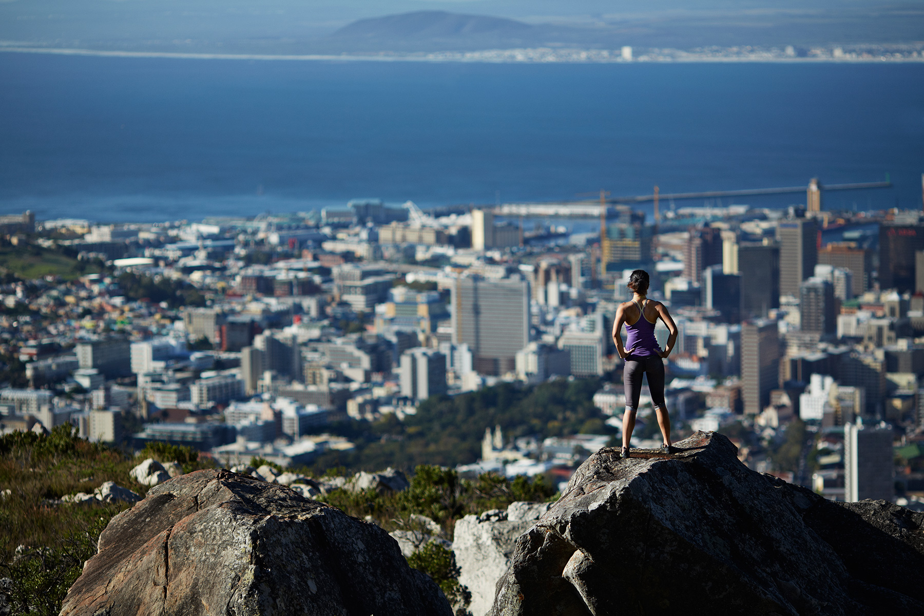 Female climber overlooking city, from top of mountain