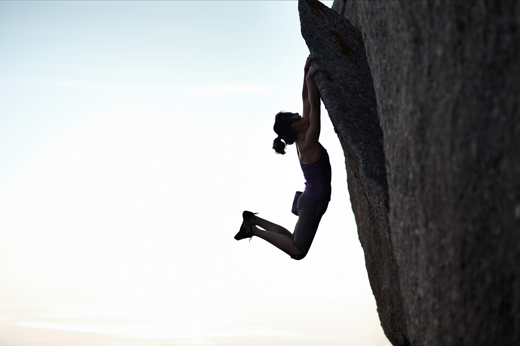 Female climber hanging on to big rock at sunset