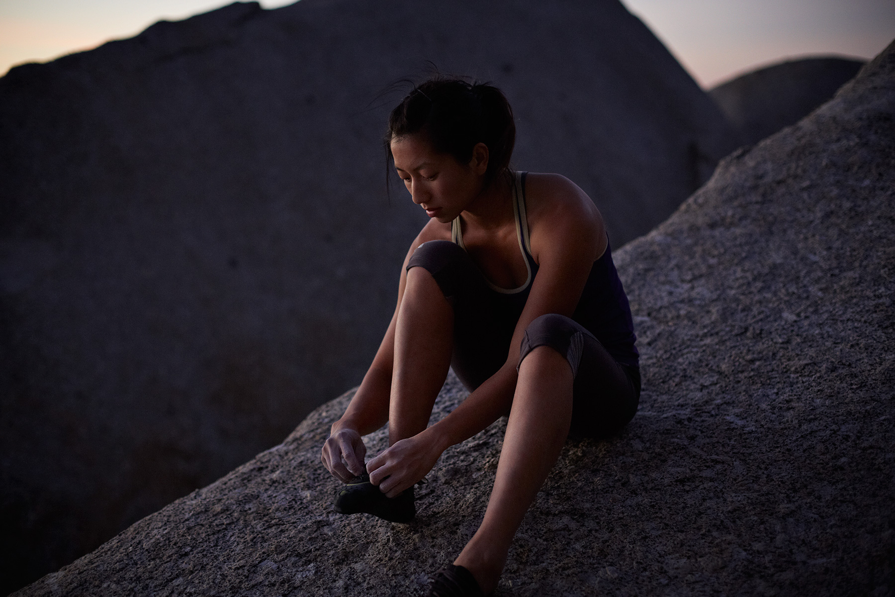 Female climber sitting on big boulder, tying shoes a
