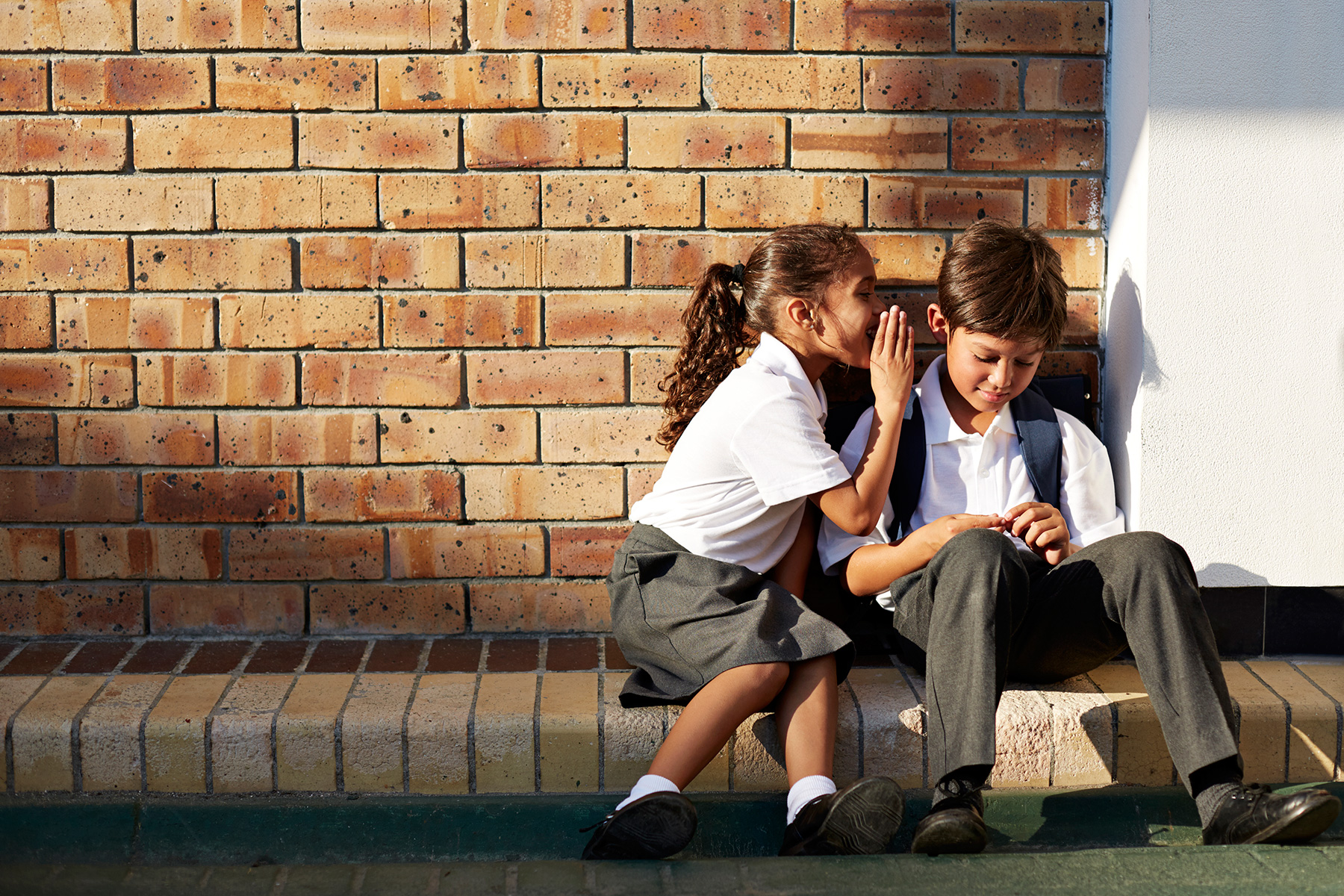 School girl whispering in friends ear in schoolyard