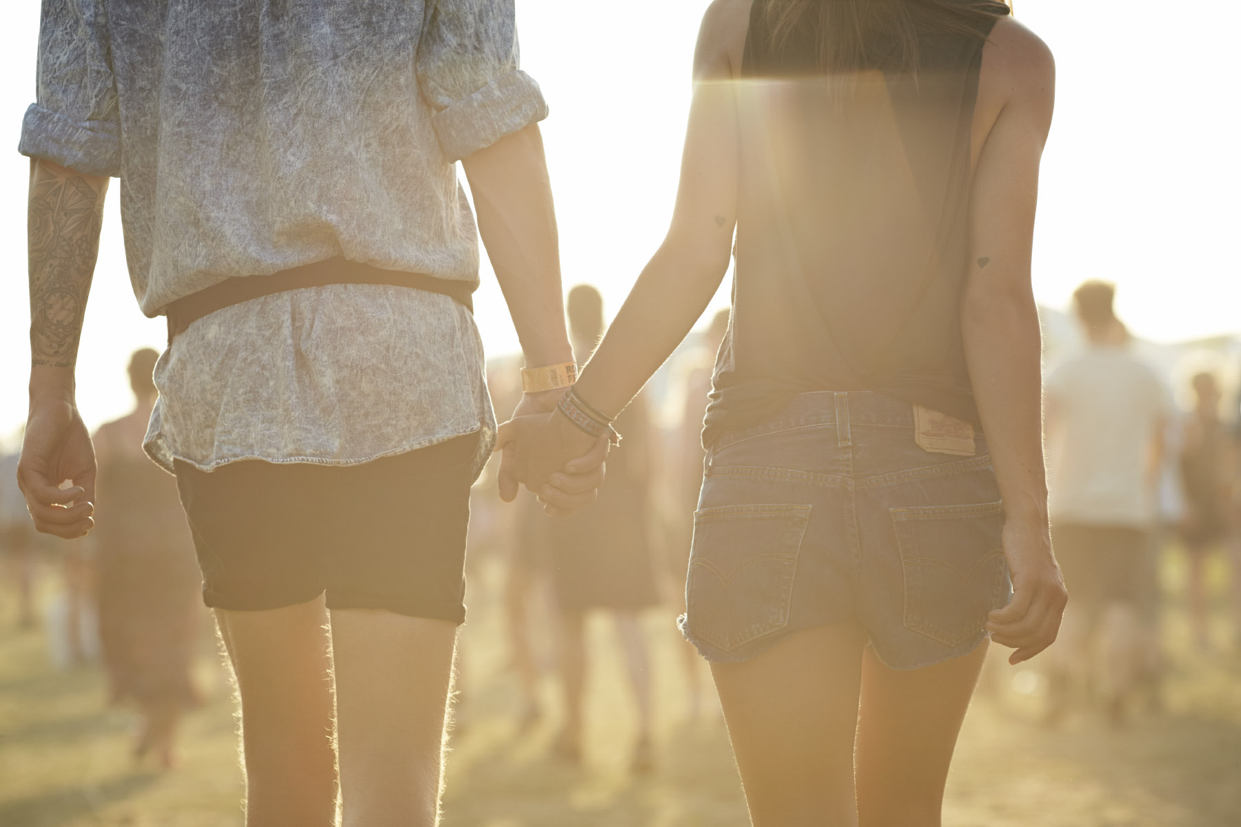 Young couple holding hands at music festival